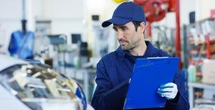 Retrato de um mecânico de carro bonito novo em uma oficina do carro, no fundo do serviço Conceito: reparo das máquinas, diâmetro  Fotos de Stock Royalty Free