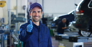 Retrato de um mecânico de carro bonito novo em uma oficina do carro, no fundo do serviço Conceito: reparo das máquinas, diâmetro  Foto de Stock Royalty Free