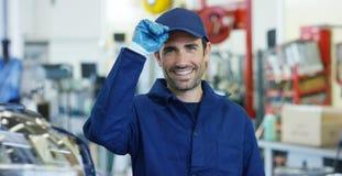 Retrato de um mecânico de carro bonito novo em uma oficina do carro, no fundo do serviço Conceito: reparo das máquinas, diâmetro  Imagens de Stock Royalty Free