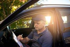 Retrato de um mecânico na escrita do rk do ¾ do wÐ na prancheta Fotos de Stock Royalty Free