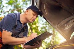 Retrato de um mecânico na escrita do rk do ¾ do wÐ na prancheta Fotografia de Stock Royalty Free