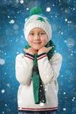 Retrato de um menino adorável da criança no chapéu e no lenço mornos do inverno em flocos de neve azuis do desenho do fundo imagens de stock