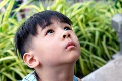 Retrato de um menino asiático curioso que olha acima no céu foto de stock