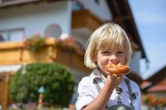 Retrato de um menino bávaro de sorriso que come o pretzel no distante Fotos de Stock