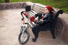 Retrato de um menino bonito do menino em um tampão-tampão vermelho, sentando-se em um banco em um parque da cidade com sua bicicl Fotografia de Stock Royalty Free