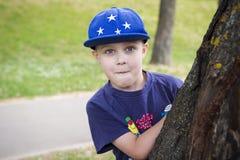 Retrato de um menino caucasiano em um tampão que espreita atrás de uma árvore Fotos de Stock Royalty Free