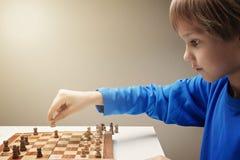 Retrato de um menino caucasiano pequeno que joga a xadrez imagem de stock royalty free