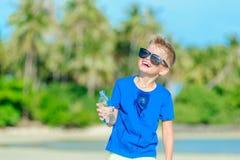 Retrato de um menino considerável sedento na água potável dos óculos de sol foto de stock