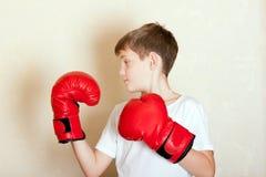 Retrato de um menino em luvas de encaixotamento vermelhas fotografia de stock