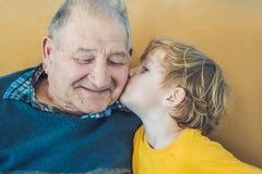Retrato de um menino feliz que beija o avô feliz Fotos de Stock Royalty Free