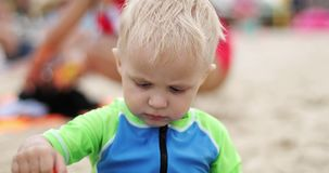 Retrato de um menino louro bonito que senta-se na praia vídeos de arquivo
