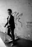 Retrato de um menino no 'trotinette' na rua urbana Fotos de Stock