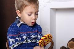 Retrato de um menino novo com um grande pirulito colorido delicioso Fotos de Stock
