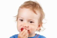 Retrato de um menino que come morangos, no fundo branco foto de stock