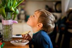 Retrato de um menino que come o café da manhã na tabela foto de stock