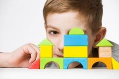 Retrato de um menino que esconde atrás da casa feita de blocos de madeira Imagem de Stock