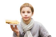 Retrato de um menino que oferece um waffle - isolado no branco Fotografia de Stock Royalty Free