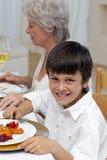Retrato de um menino que tem o jantar com sua família imagens de stock