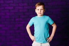 Retrato de um menino de sete anos sério em um t-shirt de turquesa e em umas calças cinzentas imagem de stock