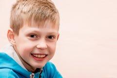 Retrato de um menino de sorriso próximo acima em um fundo cor-de-rosa obscuro, Fotografia de Stock