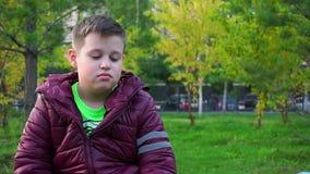 Retrato de um menino triste Sentando-se no parque, o ` s perdeu o Lento-mo vídeos de arquivo