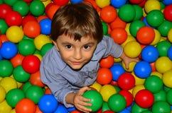 Retrato de um miúdo bonito que joga com esferas coloridas Fotografia de Stock Royalty Free