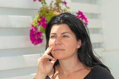 Retrato de um modelo contra um fundo da flor que tem uma expressão de pensamento fotos de stock