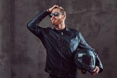 Retrato de um motociclista à moda considerável do ruivo em um casaco de cabedal preto e em óculos de sol, capacete da motocicleta imagem de stock royalty free