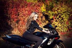 Retrato de um motociclista louro novo atrativo da mulher que levanta nela Imagens de Stock Royalty Free