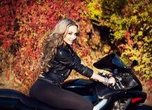 Retrato de um motociclista louro novo atrativo da mulher que levanta nela Fotos de Stock