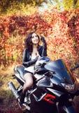 Retrato de um motociclista moreno novo atrativo da mulher que levanta em h Foto de Stock