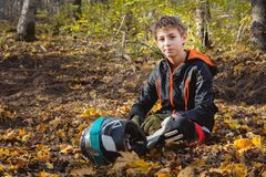 Retrato de um mtb novo do cavaleiro que senta-se na floresta em uma folha amarela que guarda um capacete da completo-cara fotos de stock royalty free