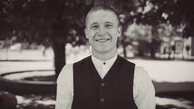 Retrato de um noivo de sorriso em uma veste preta imagem de stock