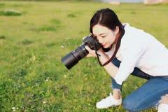 Retrato de um olhar chinês asiático do fotógrafo da mulher da natureza em sua tela da câmera em uma bordadura da floresta do parq fotos de stock