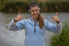 Retrato de um operador de sorriso bonito do serviço ao cliente que veste uns auriculares imagens de stock