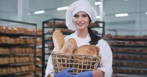 Retrato de um padeiro da senhora do país em uma indústria de padaria na frente da câmera que guarda uma cesta com pão cozido fres video estoque