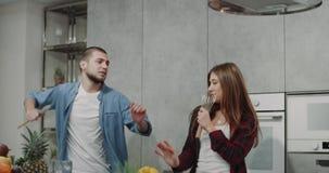 Retrato de um par carismático que canta e que dacing em uma cozinha moderna na manhã ao fazer o café da manhã filme