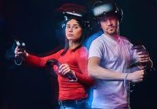 Retrato de um par caucasiano novo que levanta com auriculares e controladores de VR imagem de stock royalty free