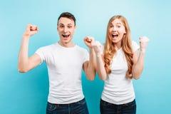 Retrato de um par entusiasmado, de um homem e de uma mulher comemorando a vitória com os punhos aumentados, gritando, em um claro fotografia de stock royalty free