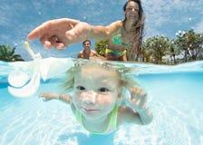 Retrato de um par feliz com a filha na piscina foto de stock