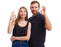 Retrato de um par feliz, gesto com as mãos que mostram tudo aprovado, isolado no fundo branco imagem de stock