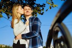 Retrato de um par feliz que abraça na rua, na cidade estando em melhor do sol, luz dura data imagem de stock