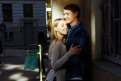 Retrato de um par feliz que abraça na rua, na cidade estar em melhor do sol data o sol brilha nas caras, co fotografia de stock royalty free