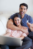 Retrato de um par feliz que registra seus feriados em linha Imagens de Stock