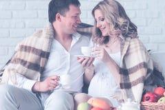 Retrato de um par novo bonito, menina grávida que come o café da manhã em casa que cobre a manta imagem de stock