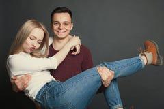 Retrato de um par novo bonito no amor que levanta no estúdio sobre o fundo escuro O indivíduo mantém o seu amado em seus braços e foto de stock