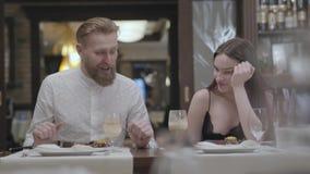 Retrato de um par novo bonito que janta em um café ou em um restaurante Os sócios comunicam-se ao relaxar em um café E filme