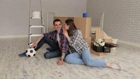 Retrato de um par novo feliz em camisas de manta em um apartamento novo filme