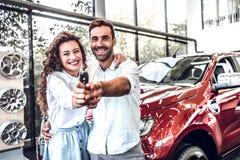 Retrato de um par novo feliz que abraça em chaves de um carro da exibição do salão de beleza do carro a um veículo recentemente c foto de stock