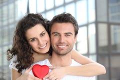 Retrato de um par novo que sorri com coração vermelho Fotografia de Stock Royalty Free